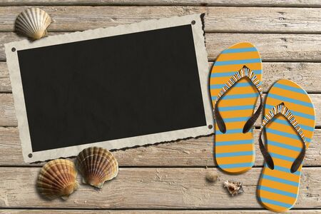 Aged picture frame with seashells on beach, flip flops sandals on wooden floor with sand photo