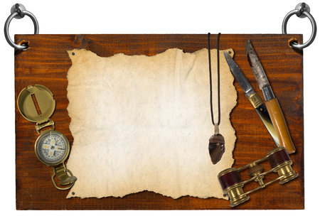 Wooden signboard hanging on to two steel rings with compass, folding knives, binoculars, flint and empty parchment photo