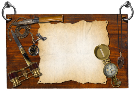 flint: Wooden signboard hanging on to two steel rings with compass, pocket watch, folding knives, binoculars, flint and empty parchment Stock Photo