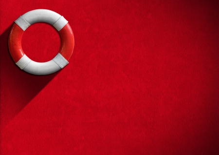 Red and white lifebuoy hanging to a red velvet wall - Concept of help photo