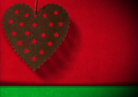 Metal heart with stars hanging on red and green velvet background with shadows photo