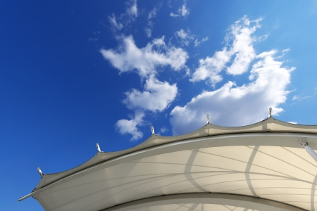 Tensile membrane fabric roof on blue sky with clouds