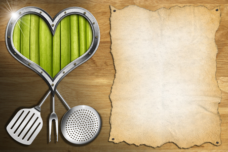 Metal porthole heart shape with green vegetables interior on wooden wall with empty parchment and kitchen utensils, template for a Vegan Menu photo