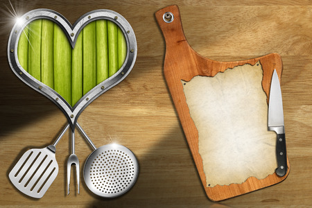 Cutting board with empty parchment, metal heart shape with green vegetables interior on wooden wall and kitchen utensils, template for a Vegan Menu photo