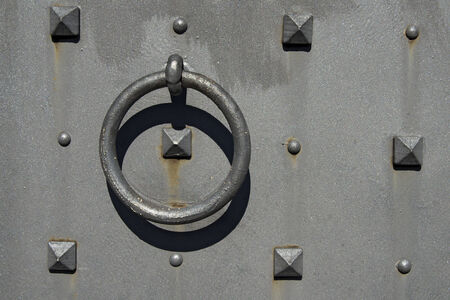 Close up of old gray metallic door with rivets, decorative nails and round handle photo