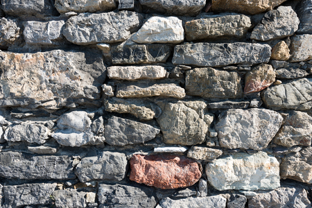 An old gray and brown stone wall makes an excellent background