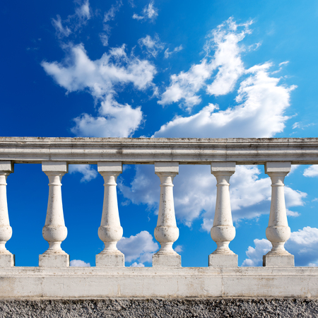 Old white stone balustrade with blue sky and clouds in the background