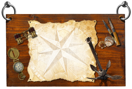 Wooden signboard with compass rose on a parchment, seashells, compass, folding knives, binoculars, and old rusty anchor  with clipping path  photo