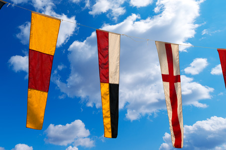0 9: Three nautical flags hanging from a rope on a blue sky with clouds - representing the numbers 0, 9, 8