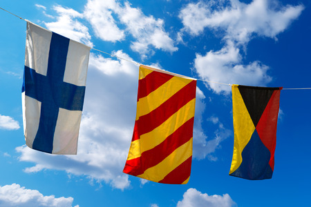 Three nautical flags hanging from a rope on a blue sky with clouds - representing to the letters XYZ