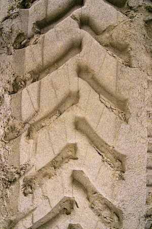 A frontal close up of industrial tractor tire tracks on beach sand photo