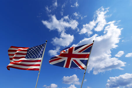 rippling: English and American flag waving in the wind on blue sky with clouds - U S A  and UK