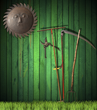 pruning shears: Green wooden wall with green grass, rake, scythe and pitchfork, pruning shears and a sun wrought iron