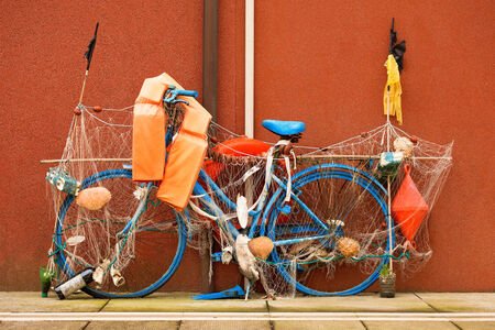 buoys: Old blue bicycle with  fishing nets, buoys, life buoys and shells in the town of Caorle  Venice  italy