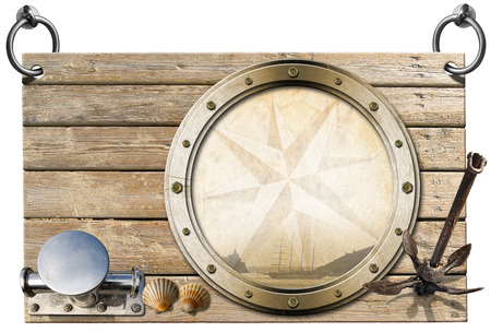 adventurous: Wooden signboard with compass rose and sailing ship on a metal porthole, seashells, old anchor and stainless mooring bitt -  concept of adventurous travels Stock Photo
