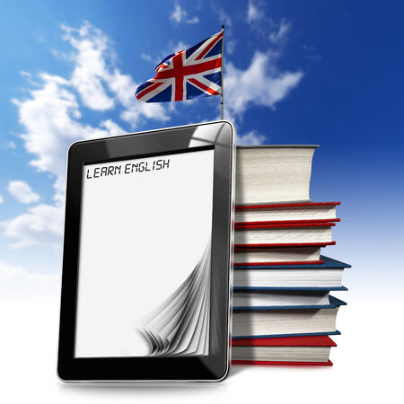 Black tablet computer with pages and word  learn english  on display, stack of books and british flag on a blue sky photo