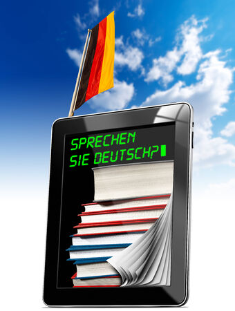 deutsch: Black tablet computer with pages and phrase  Sprechen Sie Deutsch   on display, stack of books and German flag on a blue sky Stock Photo