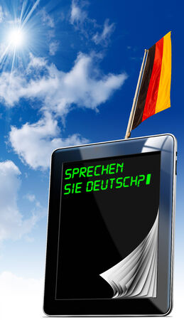 deutsch: Black tablet computer with pages and phrase  Sprechen Sie Deutsch   on display and German flag on a blue sky