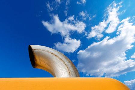 Detail of an metallic exhaust pipe of an orange excavator on blue sky with clouds photo