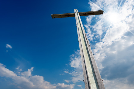 blue sky clouds: Wooden high cross with blue sky, clouds and sunlight Stock Photo