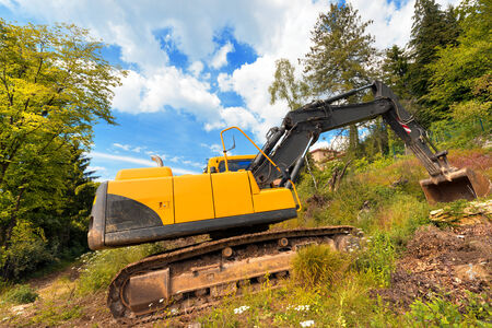 tracked: Tracked excavator yellow and black at woods and blue sky with clouds