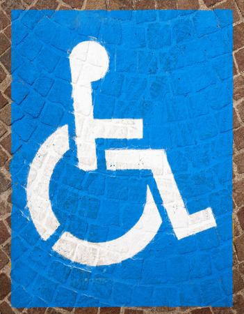 Blue and white road marking for disabled parking on floor with blocks of porphyry photo