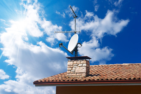 Satellite dish and TV antennas on the house roof with a beautiful blue sky