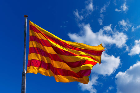 Catalan flag with pole blowing in the wind on blue sky with clouds photo
