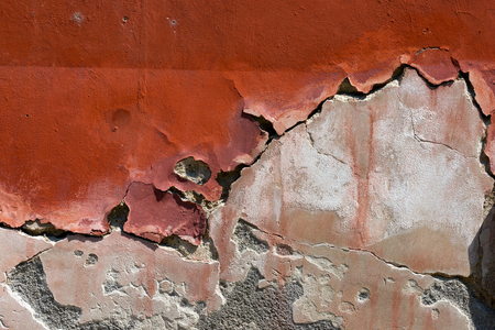 Old red, brown and white wall with cracked paint - vintage dirty wall photo