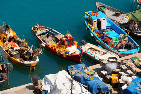 Small fishing boats, red, yellow, blue and white with fishing equipment docked in port - Lerici, La Spezia, Liguria, Italy photo
