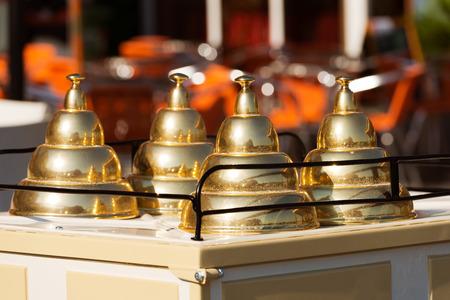pyramidal: Close up of a italian ice cream cart with three lids golden pyramid shaped