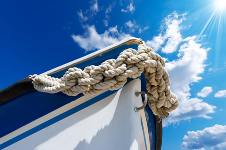 Bow of the boat adorned with knotted rope on blue sky with sun rays and space for text photo