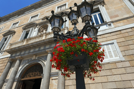 Red geraniums on a typical lamp post of Barcelona, Spain  In the background the Palau de la Generalitat de Catalunya  XV-XVII century