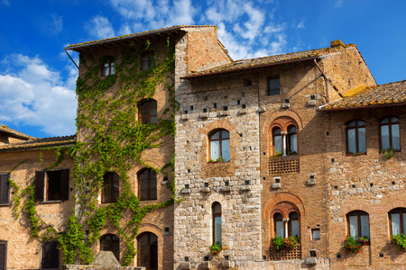 Old Buildings on the Cisterna square on blue sky, San Gimignano medieval town  UNESCO heritage , Siena, Tuscany, Italy photo