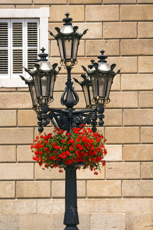 generalitat: Red geraniums on a typical lamp post of Barcelona, Spain  In the background the Palau de la Generalitat de Catalunya  XV-XVII century