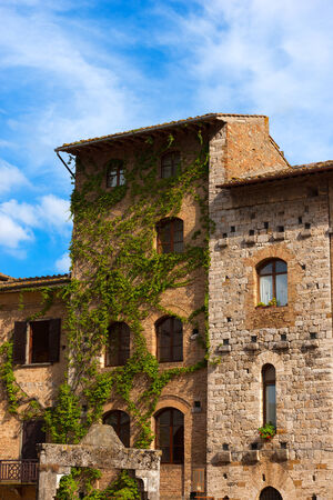 Old Buildings on the Cisterna square on blue sky, San Gimignano medieval town   , Siena, Tuscany, Italy photo