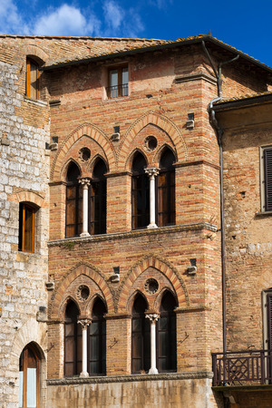 Old Buildings on the Cisterna square on blue sky, San Gimignano medieval town  UNESCO heritage , Siena, Tuscany, Italy