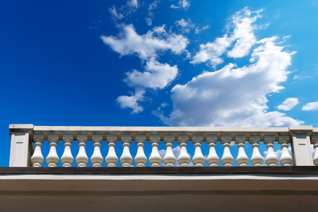 Old white stone balustrade with blue sky and clouds in the background photo