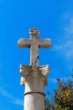 inri: Stone cross with INRI inscription on a marble column in Corinthian style on blue sky  Bonassola, Liguria, Italy Stock Photo