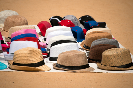 itinerant: Itinerant sales of hats resting on a cloth on the ground - Barcelona, Spain
