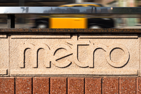 Entrance to a metro station in Barcelona and typical taxi ride in yellow and black. Catalonia, Spain photo