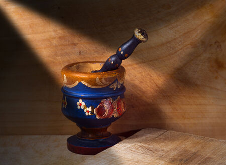 Old wooden mortar and pestle on wooden wall with chopping board photo