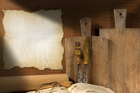 Wooden wall with cutting boards, silverware, recipe book, glasses, rolling pin and empty parchment photo