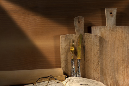 Wooden wall with two cutting boards, old silverware, recipe book, glasses and rolling pin photo