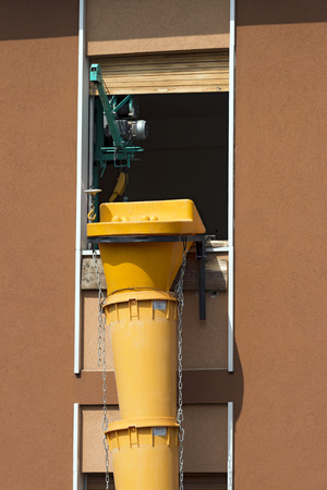Flexible pipe in yellow plastic for removing construction waste in construction site photo