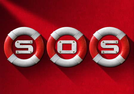 Three red and white lifebuoys hanging to a red velvet wall with the text SOS - Concept of help photo