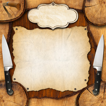 Wooden background with sections of tree trunk, two with kitchen knives, empty parchment and label. Background for a recipes or a rustic menu photo