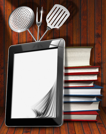 Black tablet computer with blank pages and stack of books in a kitchen, on wooden wall with kitchen utensils. For a digital recipes or menu photo