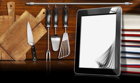 Black tablet computer with blank pages and stack of books in a kitchen, on wooden wall with kitchen utensils. Template for recipes or food menu photo