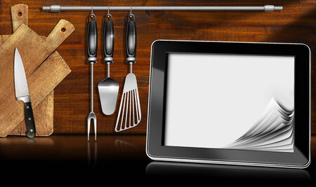 Black tablet computer with blank pages in a kitchen, on wooden wall with kitchen utensils. Template for recipes or food menu photo